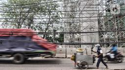 Pedagang melintas dekat instalasi kabel yang semrawut di Jalan Raya Bekasi, Cakung, Jakarta, Rabu (30/9/2020). Minimnya perawatan pascapembebasan lahan permukiman untuk proyek Tol Dalam Kota membuat jaringan kabel listrik di sepanjang jalan tersebut semrawut. (merdeka.com/Iqbal S. Nugroho)