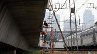 Pekerja melakukan proses pembangunan kontruksi jalur rel dwi ganda di Jakarta, Jumat (13/4). Penyelesaian proyek infrastruktur jalur DDT Manggarai- Cikarang ini ditargetkan lebih cepat dari target awal tahun 2022. (Liputan6.com/Johan Tallo)