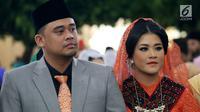 Kahiyang Ayu dan Bobby Nasution pada pesta adat pernikahan mereka di Kompleks BHR-Tasbi, Medan, Jumat (24/11). Kahiyang tampil cantik berbalut kebaya oranye, sedangkan Bobby memakai setelan jas warna abu-abu dipadu peci. (Liputan6.com/Pool/Media Center)