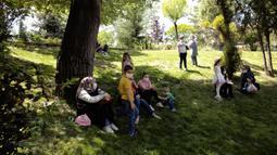 Anak-anak dengan mengenakan masker duduk bersama orang tua mereka di taman umum Kugulu di Ankara, Rabu (13/5/2020). Anak-anak diizinkan keluar rumah selama empat jam antara pukul 11.00 dan 15.00 saat Turki melonggarkan beberapa pembatasan untuk memerangi wabah virus corona. (AP/Burhan Ozbilici)