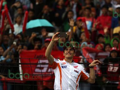 Pebalap MotoGP Repsol Honda, Marc Marquez, ber-selfie ria dengan fans yang memadati tribun Sirkuit Sentul, Bogor, Minggu (14/2/2016). (Bola.com/Nicklas Hanoatubun)