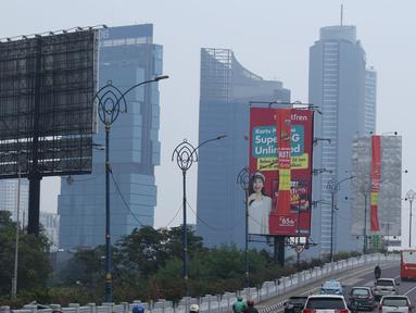 Sejumlah kendaraan melintas di sisi papan reklame di sekitar Jalan HR Rasuna Said, Jakarta, Sabtu (20/12). Pemerintah Provinsi DKI Jakarta akan menurunkan sebanyak 60 papan reklame yang dianggap melakukan pelanggaran. (Liputan6.com/Helmi Fithriansyah)