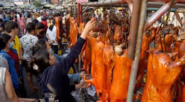 Seorang pedagang menggantung babi panggang di pasar di Phnom Penh, Kamboja (4/2). Menyambut Tahun Baru Imlek, warga Kamboja mempersiapkan daging babi panggang untuk sajian makan. (AFP Photo/Tang Chhin Sothy)