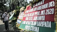 Massa dari Relawan PPDB DKI Jakarta 2020 melintas di depan karangan bunga yang terpajang di Balai Kota DKI Jakarta, Senin (6/7/2020). Karangan bunga itu bentuk kekecewaan terhadap Gubernur Anies Baswedan dan Kadisdik DKI terkait penerimaan siswa baru Jalur Zonasi. (merdeka.com/Iqbal Nugroho)