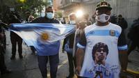 Fans Diego Maradona berkumpul di depan Rumah Sakit di La Plata, Argentina, Selasa (3/11/2020). Sejumlah fans Argentina berkumpul di depan rumah sakit untuk memberi dukungan kepada sang legenda. (AP/Natacha Pisarenko)