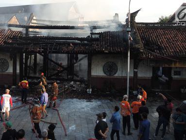 Petugas pemadam kebakaran dan warga berkumpul di lokasi kebakaran yang melanda kompleks Kelenteng Tay Kak Sie di Gang Lombok, Semarang, Kamis (21/3). Dilaporkan satu orang tewas dalam insiden kebakaran ini. (Liputan6.com/Gholib)