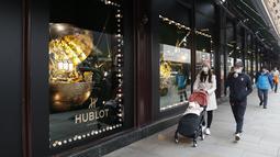 Orang-orang yang mengenakan masker berjalan melewati sebuah toko di London, Inggris, 2 Desember 2020. Sistem baru seiring berakhirnya karantina wilayah COVID-19 membagi Inggris ke dalam area-area dengan tingkat aturan pembatasan yang berbeda. (Xinhua/Han Yan)