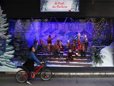 Seorang anak yang mengendarai sepeda berhenti untuk melihat etalase Natal di pusat perbelanjaan Printemps di Paris, Prancis, 22 November 2020. Deretan pusat perbelanjaan telah meluncurkan etalase Natal mereka meskipun masih tutup selama karantina wilayah kedua di seluruh Prancis. (Xinhua/Gao Jing)