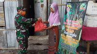 Foto : Anggota Kodim 1603 Sikka saat menyalurkan bantuan bagi warga nelayan yang terdampak covid-19 (Liputan6.com/Dion)