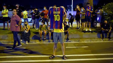 Suporter melakukan protes di depan kantor Barcelona, Selasa (25/8/2020). Aksi tersebut merupakan respon fans atas kabar Lionel Messi yang akan meninggalkan Camp Nou pada musim panas ini. (AFP/Pau Barrena)