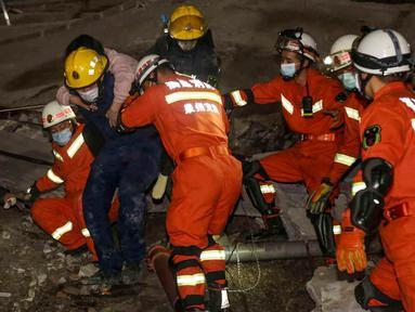 Seorang perempuan diselamatkan dari puing-puing sebuah hotel yang runtuh di Quanzhou, China, Sabtu (7/3/2020). Sekitar 70 orang terjebak di hotel Xinjia yang akhir-akhir ini digunakan sebagai tempat karantina untuk orang-orang yang berhubungan dengan pasien virus corona. (STR/AFP)