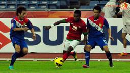Pemain Timnas Indonesia, Oktavianus Maniani (tengah) mendapat kawalan pemain Laos, Phattahana Syvilay (kanan) dan Vilayout Sayyabounsou (kiri) dalam laga Piala AFF Suzuki 2012, di Stadion Bukit Jalil, Kuala Lumpur, Malaysia. Kamis, 25/11/2012. Pertandinga