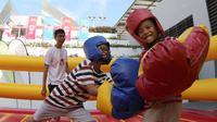 Anak-anak bermain Mega Boxing yang menjadi salah satu arena bermain di Karnaval SEA Games yang dihelat di kompleks Stadion Nasional Singapura. (Bola.com/Arief Bagus)