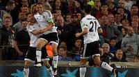Gelandang Valencia, Guilherme Siqueira (kiri) melakukan selebrasi usai Ivan Rakitic memasukan bola kegawangnya sendiri di pertandingan liga Spanyol di Camp Nou stadium (18/4). Valencia menang atas Barcelona dengan skor 2-1. (AFP PHOTO/GENE Lluis)