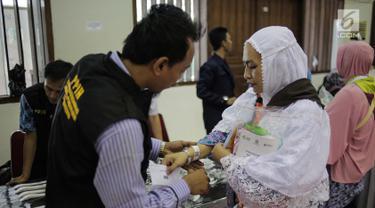 Panitia Penyelenggara Ibadah Haji (PPIH) memberikan gelang untuk calon jemaah haji kloter pertama di Asrama Haji, Jakarta, Sabtu (6/7/2019). Sebelum diberangkatkan, petugas mengecek kembali 385 calon jamaah untuk melakukan kelengkapan administrasi. (Liputan6.com/Faizal Fanani)