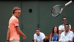 Petenis Jerman, Alexander Zverev melempar raketnya ketika kehilangan servis pada babak kedua Prancis Terbuka di Stade Roland Garros, Rabu (30/5). Zverev harus bermain selama 3 jam 24 menit mengatasi petenis Serbia, Dusan Lajovic. (AP/Alessandra Tarantino)