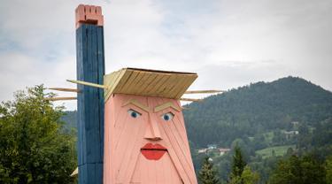 Sebuah patung kayu yang menyerupai Donald Trump didirikan di Sela pri Kamniku, kawasan utara Slovenia, 30 Agustus 2019. Patung Trump setinggi 8 meteritu mengenakan setelan biru, kemeja berwarna putih, dasi merah, serta mengangkat tangan seperti Patung Liberty. (AP/Darko Bandic)