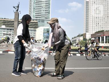 Aktivis yang tergabung dalam Sekolah Relawan memunguti sampah saat aksi Jakarta Clean Action selama Hari Bebas Kendaraan Bermotor (HBKB) di kawasan Bundaran HI, Jakarta, Minggu (1/12/2019). (merdeka.com/Iqbal S. Nugroho)
