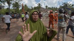 Seorang wanita berlari mencari tempat perlindungan saat terjadi gempa susulan di Tanjung pulau Lombok, NTB, Kamis (9/8). Menurut BNPB pusat gempa berada di enam kilometer barat laut Lombok Utara dengan kedalaman 12 kilometer. (AFP/ ADEK BERRY)