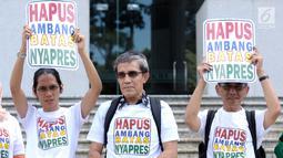 Sebagian dari pemohon pengajuan uji materi Pasal 222 UU No.7 Tahun 2017 mengangkat tulisan di depan Gedung Mahkamah Konstitusi, Jakarta, Kamis (21/6). Mereka mengajukan uji materi syarat ambang batas pencalonan presiden. (Liputan6.com/Helmi Fithriansyah)
