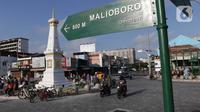 Pengendara melintas di perempatan Tugu Pal Putih Yogyakarta, Sabtu (26/12/2020). Dilansir Visiting Jogja, tugu yang dibangun pada 1755 oleh Hamengkubuwono I ini merupakan garis yang bersifat magis yang menghubungkan laut selatan, Kraton Jogja, dan Gunung Merapi. (Liputan6.com/Helmi Fithriansyah)