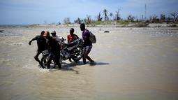 Sejumlah pria membantu warga menggotong sepeda motornya menyeberangi sungai di Les Anglais, 10 Oktober 2016. Selain merusak ribuan rumah, badai Matthew di Haiti juga memutus jembatan yang merupakan akses utama warga. (REUTERS/Andres Martinez Casares)