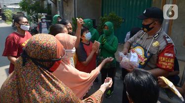 Polisi membagikan masker kepada warga RW 11, Kelurahan Pondok Kopi, Jakarta, Jumat (18/9/2020). Di masa pandemi COVID-19, TNI dan Polri bersinergi mengimbau warga untuk mematuhi protokol kesehatan dengan memakai masker saat beraktivitas di luar rumah. (merdeka.com/Imam Buhori)