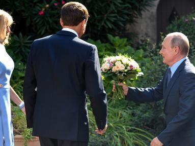 Presiden Rusia Vladimir Putin (kanan) berlutut memberi bunga kepada istri Presiden Prancis Emmanuel Macron (tengah), Brigitte Macron (kiri) di Benteng Bregancon, Bormes-les-Mimosas, Prancis, Senin (19/8/2019). Putin diketahui kerap memberi bunga kepada wanita. (Gerard Julien, Pool via AP)
