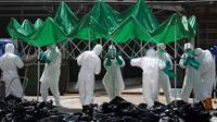 Sejumlah petugas menyiapkan tenda untuk memisahkan unggas di sebuah pasar di Hong Kong, (7/6).  Pihak berwenang memutuskan untuk menangguhkan perdagangan unggas hidup setelah pemeriksaan menunjukkan adanya virus flu burung H7N9. (REUTERS/Bobby Yip)