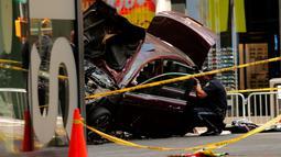 Petugas memotret kondisi mobil yang menabrak para pejalan kaki di trotoar Times Square, New York, Kamis (18/5). Para saksi mata menyebut mobil itu melaju melawan arus sebelum menabrak para pejalan kaki hingga melukai sekitar 22 orang. (Jewel SAMAD/AFP)