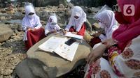 Siswa kelas 3 SDN II Roda Kota Bogor dan pendamping yang memiliki smartphone belajar kelompok secara daring di pinggir sungai Ciliwung, Kampung Kebon Jukut RT 01/10, Babakan Pasar, Kamis (6/8/2020). Kegiatan itu untuk mendapatkan jaringan internet yang baik di masa pandemi. (merdeka.com/Arie Basuki)
