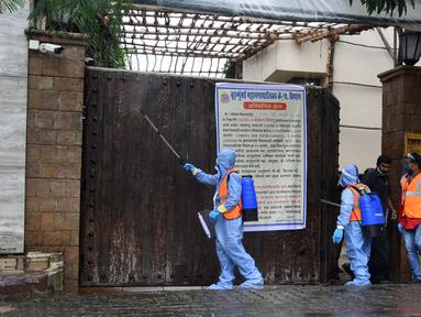 Pekerja otoritas sipil menyemprot disinfektan di pintu utama kediaman bintang Bollywood Amitabh Bachchan saat ia dinyatakan positif COVID-19 di Mumbai (12/7/2020).  Amitabh Bachchan dan putranya Abhishek Bachchan terpapar virus Corona Covid-19. (AFP/Sujit Jaiswal)