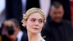 "Elle Fanning berpose saat tiba menghadiri screening film ""Les Miserables"" dalam acara Festival Film Cannes ke-72 di Prancis (15/5/2019). Elle Fanning tampil dengan tatanan rambut kepang milkmaid oleh hairstylist Jenda Alcorn. (AP Photo/Arthur Mola)"