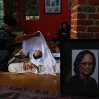 Salah seorang membuka kain putih penutup kepala lelaki yang memiliki nama asli Koesyono Koeswoyo itu. Suasana duka menyelimuti kediamannya di kawasan Tangerang Selatan. (Adrian Putra/Bintang.com)