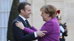 Presiden Prancis Emmanuel Macron (kiri) menyambut Kanselir Jerman Angela Merkel saat tiba di Istana Presiden Eylsee di Paris (16/3). Prancis ingin agar Uni Eropa menggunakan anggaran lebih besar untuk menggerakkan ekonomi. (AFP Photo/Ludovic Marin)