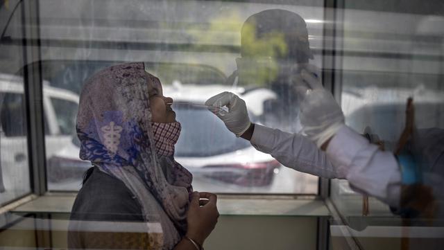 Seorang petugas kesehatan mengambil sampel usap untuk menguji COVID-19 di rumah sakit pemerintah di Noida, pinggiran New Delhi, India, Rabu (7/4/2021). India mencapai puncak baru dengan 115.736 kasus COVID-19 dalam 24 jam. (AP Photo/Altaf Qadri)