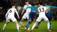 Pemain Arsenal, Mesut Ozil berusaha merebut bola dengan kawalan pemain Swansea City dalam laga pekan ke-25 Premier League 2017-2018 di Liberty Stadium, Selasa (30/1). Arsenal dipaksa menyerah Swansea City 1-3. (Nick Potts/PA via AP)