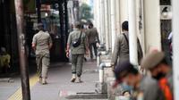 Petugas Satpop PP berpatroli di kawasan Pasar Tanah Abang, Jakarta, Rabu (7/7/2021). Satpol PP melakukan penjagaan di seluruh Pasar Tanah Abang mengantisipasi pedagang yang membandel tetap berjualan saat diberlakukannya PPKM Darurat. (Liputan6.com/Angga Yuniar)
