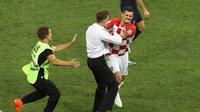 Seorang penyusup mendekati bek timnas Kroasia, Dejan Lovren dalam laga final Piala Dunia 2018 melawan Prancis di Luzhniki Stadium, Minggu (15/7). Pertandingan sempat dihentikan sebelum para penyusup ditangkap oleh petugas. (AP/Thanassis Stavrakis)