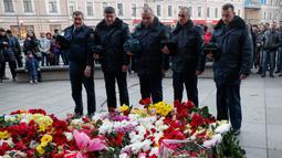 Sejumlah petugas melakukan bela sungkawa atas tragedi bom yang meledak di stasiun kereta bawah tanah St. Petersburg, Rusia, Selasa (4/4). Dikabarkan 10 orang meninggal dalam tragedi tersebut. (AP Photo / Dmitri Lovetsky)