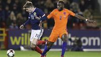 Pemain Skotlandia, Ryan Christie (kiri) mencoba melewati adangan pemain Belanda, Timothy Fosu-Mensah pada laga persahabatan di Pittodrie, Aberdeen, Skotlandia (9/11/2017). Belanda menang 1-0. (Andrew Milligan/PA via AP)