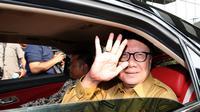 Mendagri Tjahjo Kumolo melambaikan tangan saat meninggalkan Gedung KPK, Jakarta, Senin (26/2). Tjahjo mengaku kedatangannya memenuhi undangan pimpinan KPK. (Liputan6.com/Helmi Fithriansyah)