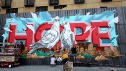 """Para seniman mengerjakan mural yang menggambarkan Kota Beirut dengan kata """"HOPE"""" (harapan) di Beirut, Lebanon, 4 September 2020. Pemuka agama Islam dan Kristen beserta warga mengadakan doa bersama dekat silo-silo gandum yang hancur di Pelabuhan Beirut. (Xinhua/Bilal Jawich)"""