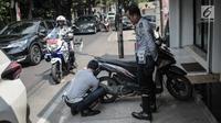 Petugas Dishub DKI Jakarta merazia  kendaraan roda dua dengan mencopot pentil yang terparkir di trotoar di kawasan Cipete Raya, Jakarta, Selasa (13/8/2019). Razia tersebut dilakukan Dishub untuk mengembalikan fungsi trotoar