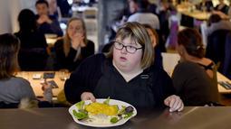"""Seorang pelayan dengan down syndrome bersiap mengantar pesanan kepada pengunjung restoran """"Le Reflet"""" di Nantes, Prancis Barat, 9 Februari 2017. Lelievre (26), mempekerjakan sejumlah karyawan yang memiliki down syndrome di restorannya. (LOIC VENANCE/AFP)"""