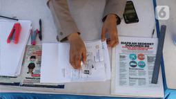 Petugas memeriksa kelengkapan dokumen penumpang yang menyeberang dengan kapal ferry di Pelabuhan Merak, Banten, Senin (18/5/2020). Penumpang harus memenuhi sejumlah persyaratan ketat mencakup standar kesehatan dan verifikasi dokumen guna memutus rantai penyebaran COVID-19 (Liputan6.com/Angga Yuniar)
