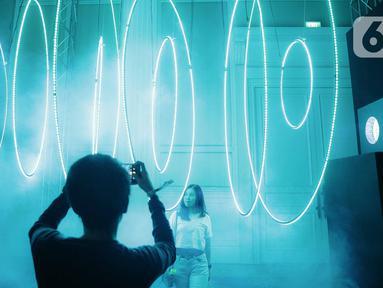 Pengunjung berpose saat mengunjungi pameran seni berbasis teknologi berwujud sorotan cahaya futuristik 'Wave of Tomorrow' di Jakarta, Sabtu (21/12/2019). Pameran seni Wave of Tomorrow' menghadirkan 14 karya seni media baru dari 13 kreator Tanah Air dan internasional. (Liputan6.com/Faizal Fanani)