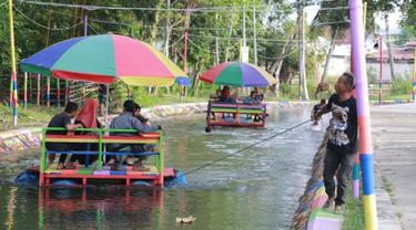 Wisatawan menaiki perahu apung di Wisata Air Toino, Desa Talulobutu, Kecamatan Tapa, Kabupaten Bone Bolango, Gorontalo, Sabtu (30/3). Warga sekitar menyulap drainase ini menjadi tempat wisata yang unik. (Liputan6.com/Arfandi Ibrahim)