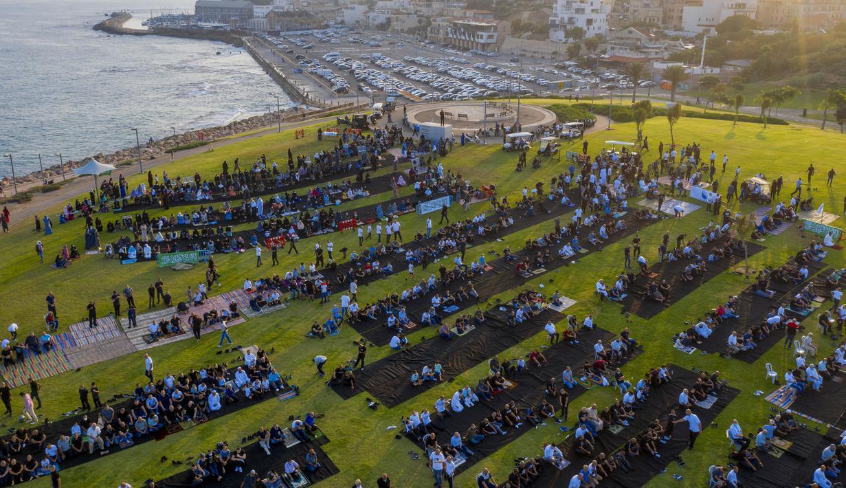 Umat muslim berkumpul melaksanakan salat Idul Adha di sebuah taman kota campuran Yahudi dan Arab, Jaffa, Israel, Jumat (31/7/2020). Ini adalah Idul Adha pertama sejak awal pandemi COVID-19. (AP Photo/Oded Balilty)