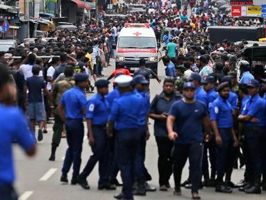 Polisi mensterilkan jalan saat sebuah ambulans melaju membawa korban ledakan gereja di Kochchikade, Kolombo, Sri Lanka, Minggu (21/4). Sekitar 99 orang dilaporkan tewas dalam ledakan di tiga gereja dan tiga hotel di Sri Lanka. (AP Photo/Eranga Jayawardena)